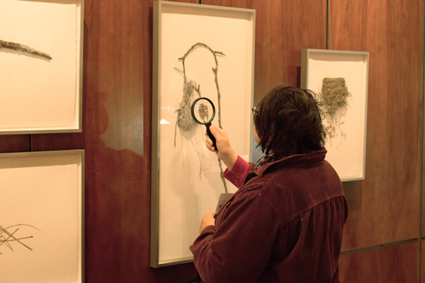 <p>Visitor Angella Bradick examining David Morrison's drawing, 20 March 2015, photo by Frank A. Reynolds, reproduced by permission of the photographer.</p>