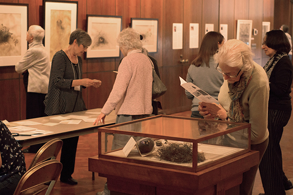 <p>Visitors discuss vellum with Kate Nessler and explore the gallery, 20 March 2015, photo by Frank A. Reynolds, reproduced by permission of the photographer.</p>
