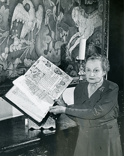 <p>Rachel Hunt (1882–1963), holding a Spanish manuscript of music dated 1458, bound over wood boards in red-tooled leather (now in Hunt Library's Fine and Rare Books Collection), ?at Elmhurst, 1962, photograph by Jones of East Liberty, HI Archives portrait no. 21.</p>